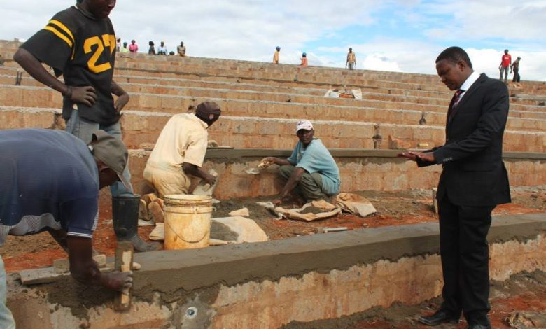 Workers are building steps or seats in a Stadium and look up to a man in a nice suit who is talking and gesticulating
